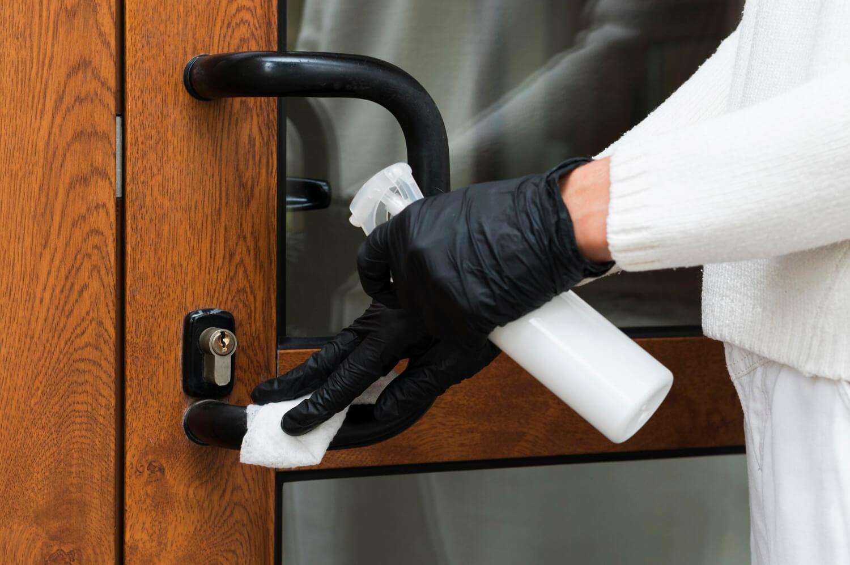 hands-with-gloves-disinfecting-door-handle